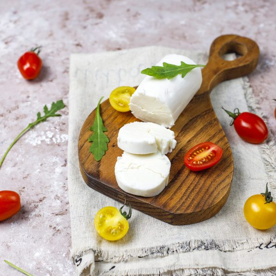 Goat Cheese Slices on Wooden Board with ruccola,cherry tomatoes.